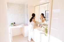 鏡の前で肌を見る女性
