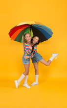 Carefree And Happy. Two Happy Kids Yellow Background. Children Enjoy Rainy Autumn. Fall Kid Fashion. Feeling Safe And Comfortable. Good Mood At Any Weather. Small Girl Under Colorful Umbrella