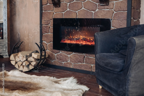 View over fireplace with burning logs, natural fur skin on the floor next to holder with logs in cozy room Poster Mural XXL