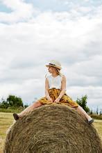 Girl Sitting On Bale Of Hay