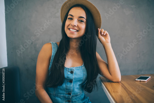 Fotografie, Tablou  Half length portrait of cheerful hipster girl in stylish fashionable apparel loo