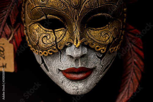 Photo wooden mask on black background colour red and gold
