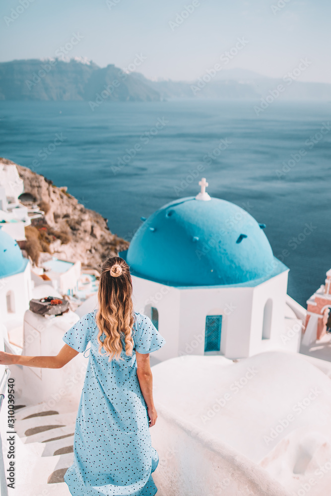Fototapeta Young woman with blonde hair and blue dress in oia, santorini, greece with ocean view and churches