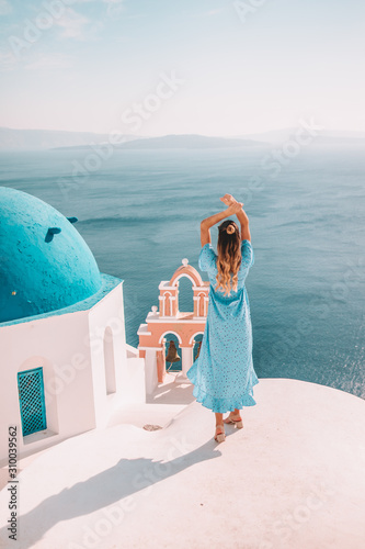 Young woman with blonde hair and blue dress in oia, santorini, greece with ocean Canvas Print
