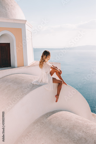 Fototapeta Young woman with white dress on rooftop in santorini greece obraz