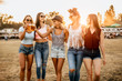 canvas print picture - Female friends cheering with beer while arriving at the music festival