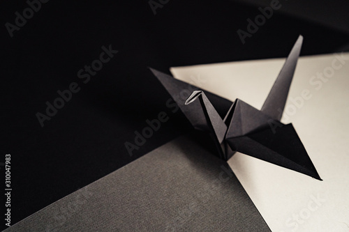 Fotografie, Obraz origami crane made of dark gray paper stands on sheets of paper