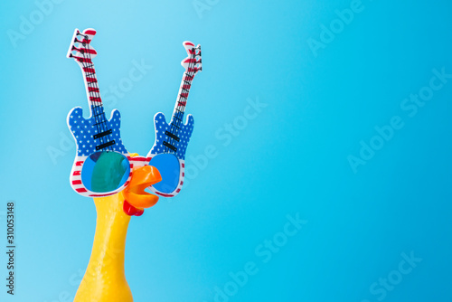 Fényképezés Screaming toy chicken in glasses on a blue background