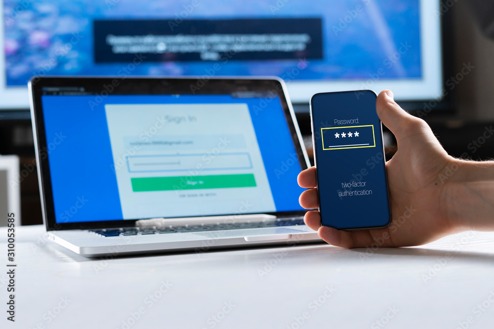 Fototapeta holding a phone and working using laptop, log in on website, double-factor authentication interface