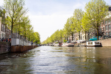 Amsterdam Canal With Traditional Old Houses And Trees.Landscape And Culture Travel, Or Historical Building And Sightseeing Concept.