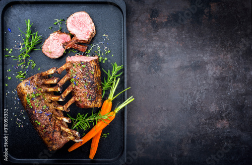 Fotografía  Barbecue rack of lamb with carrot and herbs offered as top view on a modern desi