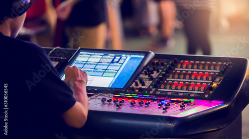 Technicians are controlling the sound system and lighting system on the concert stage. The sound engineer is controlling the system at the control panel.