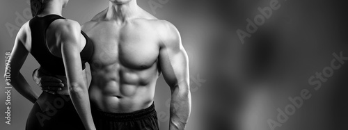 Foto A young man with muscular torso and sporty woman on black background