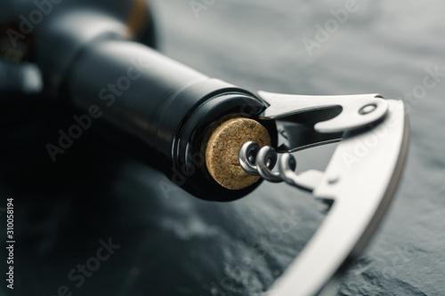 Cuadros en Lienzo Stainless  wine corkscrew in a cork of wine bottle neck on a black slate backgro