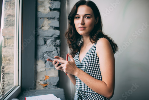 Vászonkép Half length portrait of attractive female blogger with mobile device in hand loo