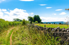 A Footpath By A Stone Wall In The English Countryside In Summer