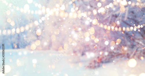 Christmas blurred background. Xmas trees with snow decorated with garland lights, holiday festive background. New year Winter art design, Christmas scene holiday blur forest backdrop