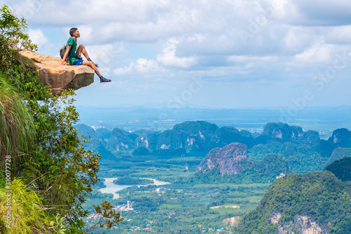 Photo Young traveler sits on a rock that overhangs the abyss, with a beautiful landscape below