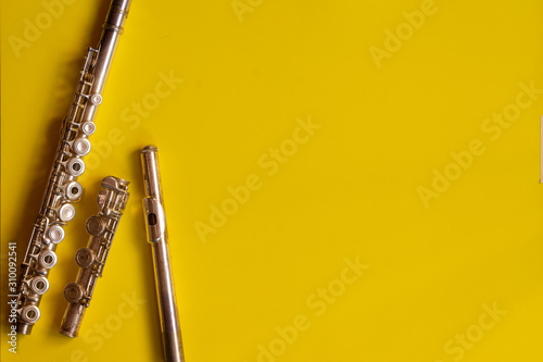 Top view flute traverse over yellow background. music concept flutist player.