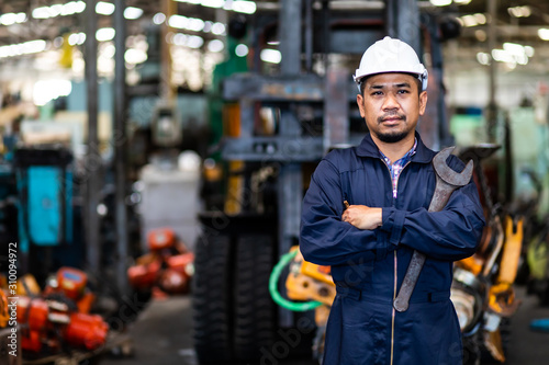 Portrait of Asian mechanic Fold over holding a wrench and smiling at truck and forklift garage. Industrial mechanic Engineer in Hard Hat