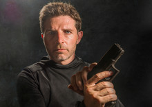 Action Portrait Of Serious And Attractive Hitman Or Special Agent Man Holding Gun Reloading The Weapon Isolated On Dark Background In Secret Service Hollywood Style Movie