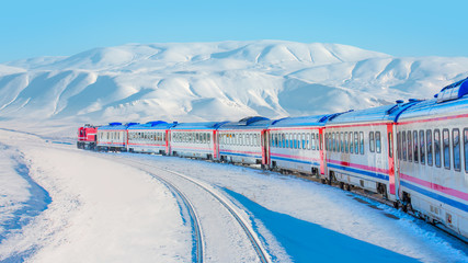 Red diesel train (East express) in motion at the snow covered railway platform - The train connecting Ankara to Kars - Turkey
