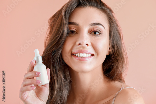 Fotomural  Beautiful young woman with bottle of serum on color background
