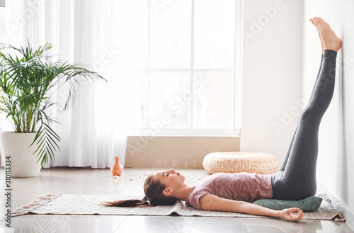 Beautiful young woman practicing yoga at home Canvas Print