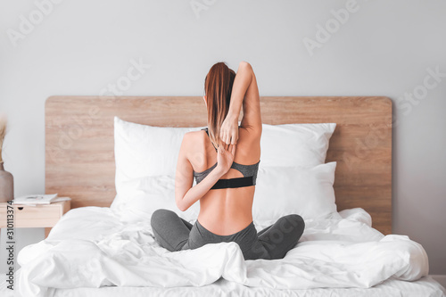 Beautiful young woman practicing yoga in bedroom - 310113374