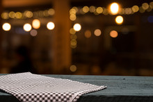 Empty Wooden Deck Table With Tablecloth Over Bokeh Background
