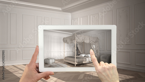 Fototapeta Augmented reality concept. Hand holding tablet with AR application used to simulate furniture and design products in empty interior with parquet floor, classic bedroom with canopy bed obraz