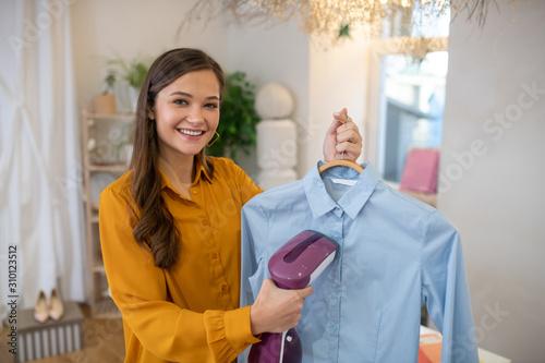 Pleasant positive young woman ironing her shirt Fototapeta