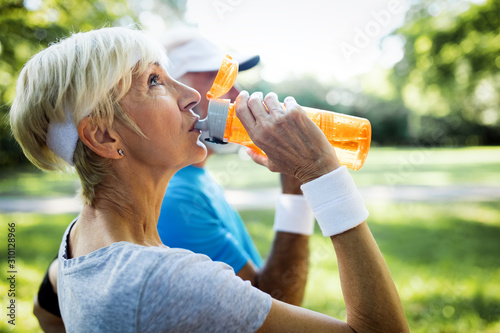 Mature couple drinks water to replenish energy and to hydrate - 310128966