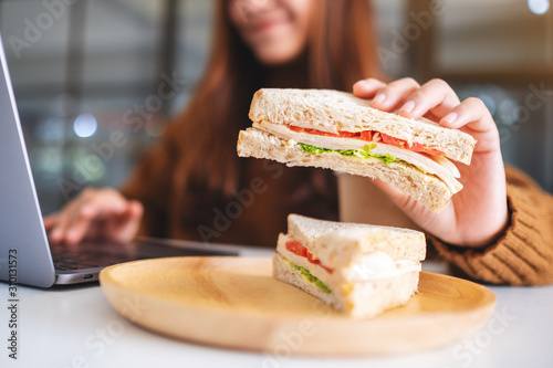 An asian woman holding and eating whole wheat sandwich while working on laptop computer