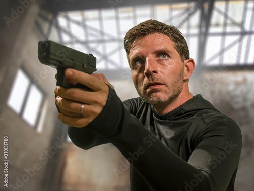 Carta da parati action portrait of serious and attractive hitman or special agent man holding gu