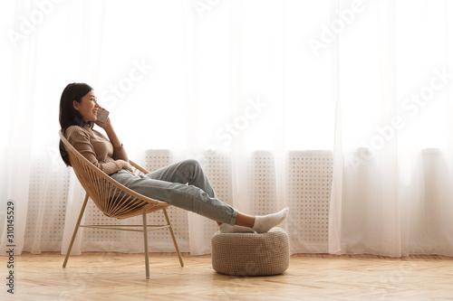 Fototapeta Teen girl relaxing in modern armchair and talking on phone obraz na płótnie