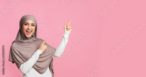 Obraz na plátně  Cheerful muslim woman pointing at copy space on pink background