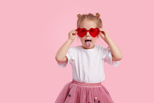 Portrait Of Surprised Cute Little Toddler Girl In The Heart Shape Sunglasses. Child With Open Mouth Having Fun Isolated Over Pink Background. Looking At Camera. Wow Funny Face.