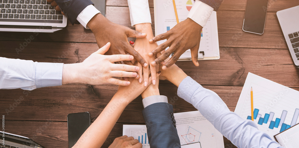 Fototapeta Multiethnic coworkers stacking hands together in office