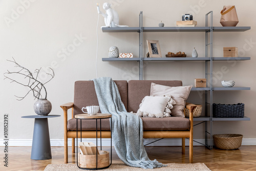 Modern interior design of living room with brown wooden sofa, gray bookstand, vase with flowers, coffee table, decoration and elegant accessories. Beige and japandi concept. Stylish home staging.  - 310152392