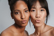 Portrait closeup of two multinational half-naked women making kiss lips
