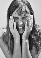 Woman Laughing Whilst Being Splashed By Water. Female Holding Her Face Whilst Smiling. Black And White Portrait Of Female Model Laughing.
