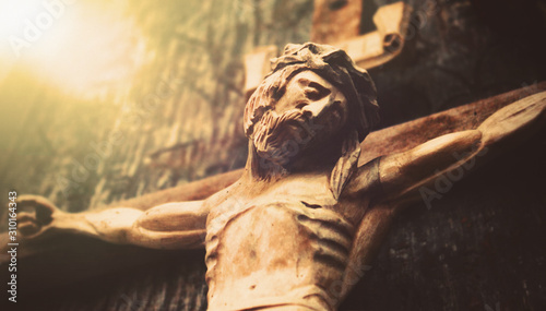 Fotografija Antique wooden statue of crucified Jesus Christ against dark wooden background