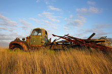 Old Truck Abandoned In A Field Of Waving Grass Beneath A Cloudy Blue Sky.