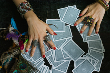 Top view close up hands of  fortuneteller with   tarot cards on wooden table.  Divine magic & occultism concept.