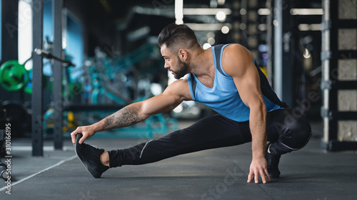 Fotografía  Young athlete stretching legs before training at gym