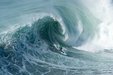 Surfer Riding Forward The Moving Foamy Wave Of The Atlantic Ocean At Nazare, Portugal
