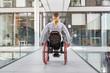 Frau im Rollstuhl im behindertengerechten Bürohaus