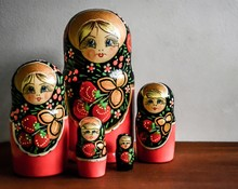 Wooden Table With Russian Nesting Matrioshka Dolls With A White Background