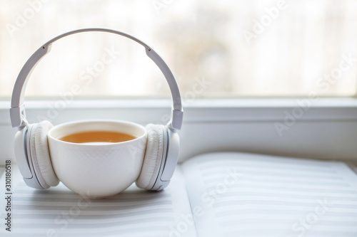 white headphones with a cup of tea on the window - 310180518